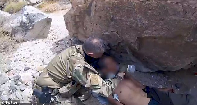 A Border Patrol agent provides water to a 55-year-old man from Mexico who was abandoned by human smugglers in the California mountains on August 13