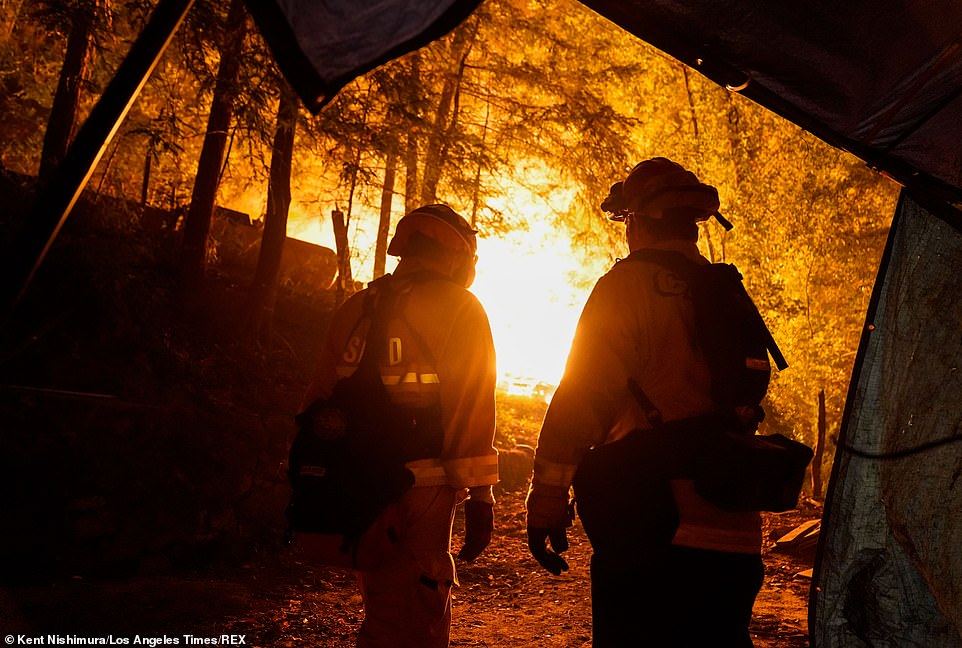 Three massive wildfires are raging in Northern California as 250,000 people are under evacuation orders and seven have been killed. Firefighters respond to a structure fire in part of the CZU Lightning complex in Boulder Creek, California on Sunday