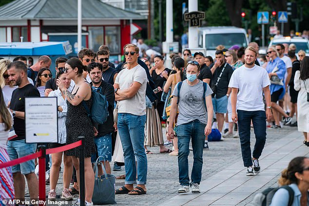 A man wearing a face mask walks past a line of people not wearing masks as they wait to board a boat atStranvagen in Stockholm. Mask sales have soared in the past three weeks since the public health agency suggested they might be of benefit
