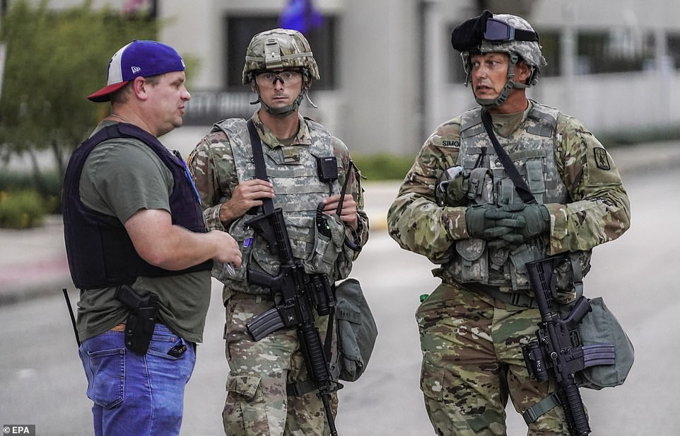 Two members of the Wisconsin National Guard talk to a police officer, left, during a third night of unrest Tuesday in the wake of the shooting of Jacob Blake by police officers