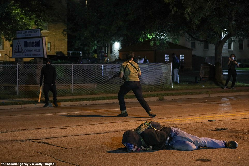 A man on the ground was shot in the chest as clashes between protesters and armed civilians who protect the streets of Kenosha against the arson during the third day of protests over the shooting of a black man Jacob Blake by police officer in Wisconsin, United States in the early hours of this morning