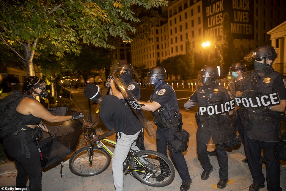Protests continued Sunday night in Washington DC, with videos emerging online of protesters clashing with police in the street and shining lights into the homes of residents chanting, 'Are you home, get into the street