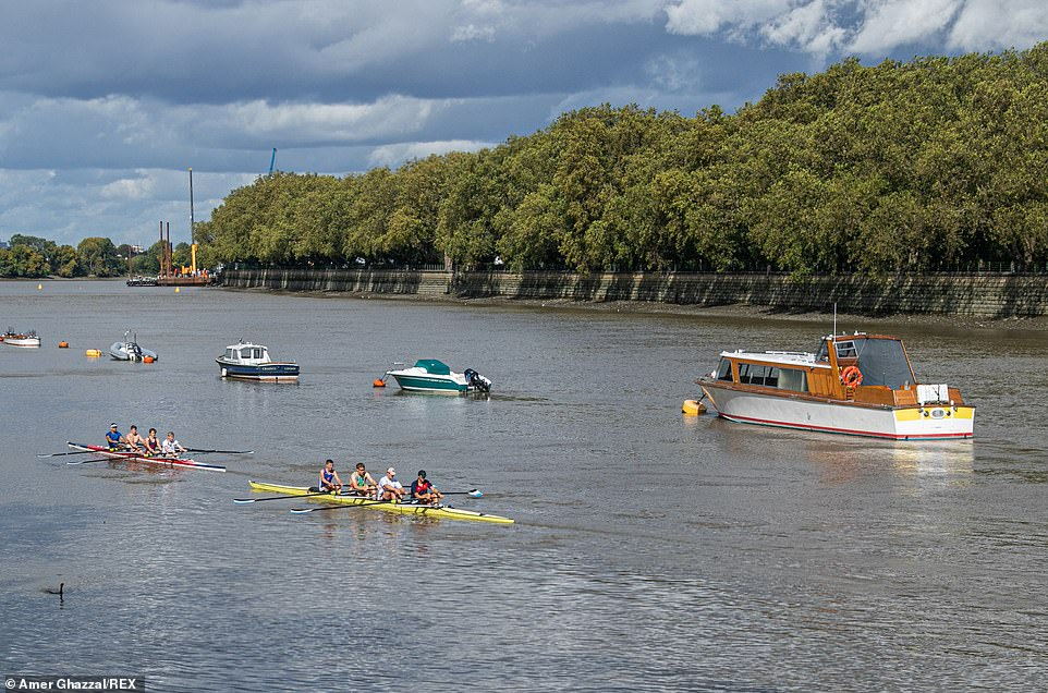 Rowers on River Thames by Putney riverside on a mixed day with rain showers and sunny spells in South West London today