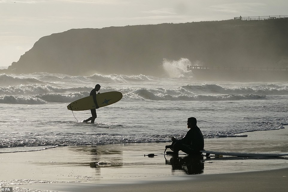 Surfers walk and sit among the waves off Tynemouth today ahead of strong winds arriving in eastern England tomorrow