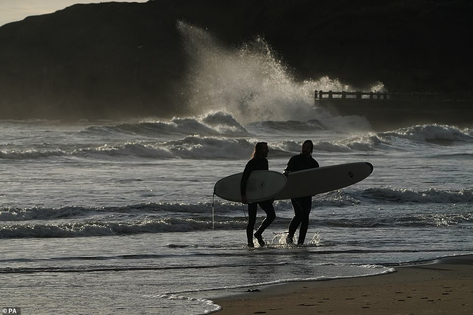 Surfers walk through the water as they make the most of the waves off Tynemouth in Tyne and Wear this morning