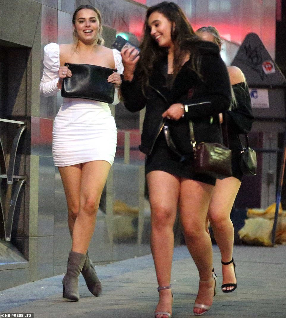 Three women walk down a street in Leeds city centre as they meet up with friends for a night out ahead of new restrictions on Saturday