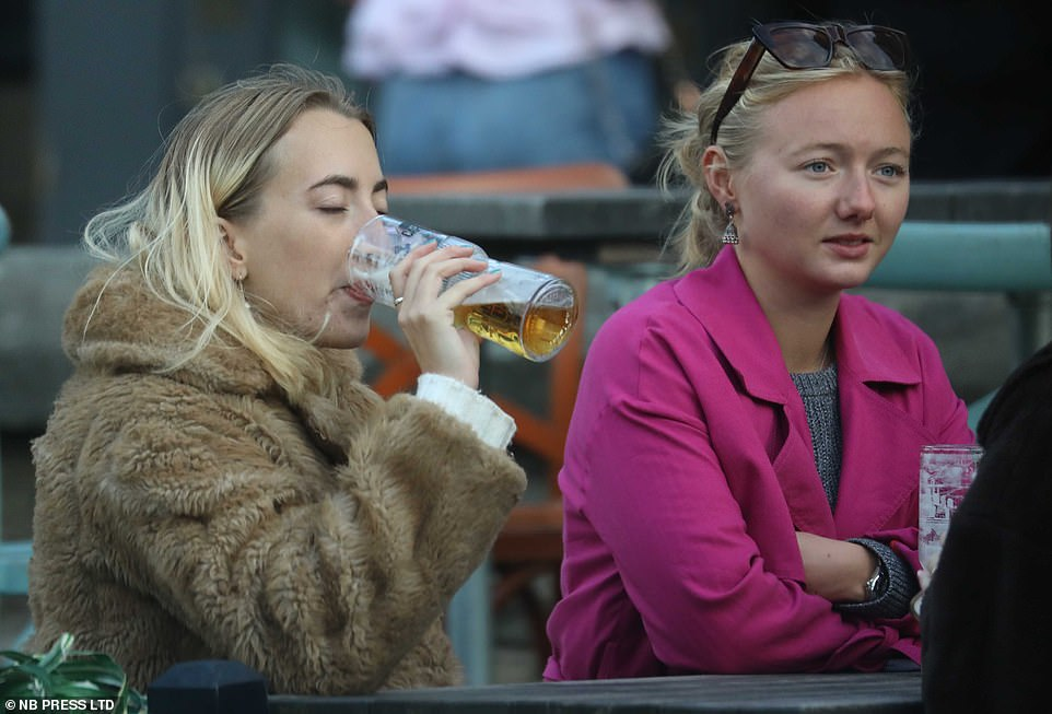 One woman sinks a pint as another watches on as people flocked to pubs, bars and restaurant in Leeds ahead of new restrictions on Saturday