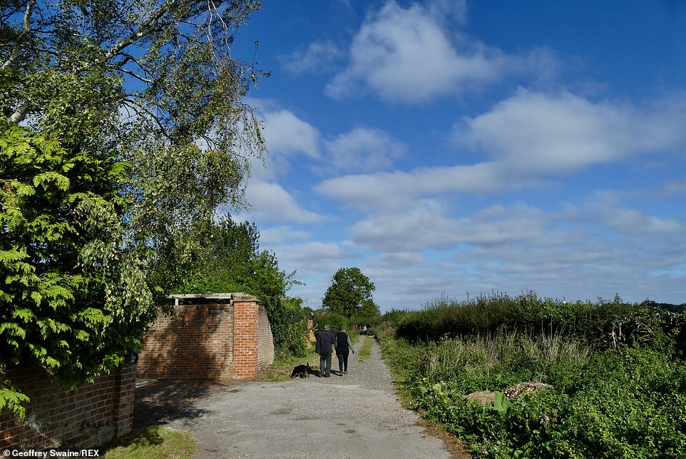 East Anglia, the south east of England and Yorkshire experienced a cold and cloudly weekend with rain and strong northerly winds, while the rest of the country enjoyed blue sky and crisp, autumnal weather (Pictured: walkers in Oxfordshire)