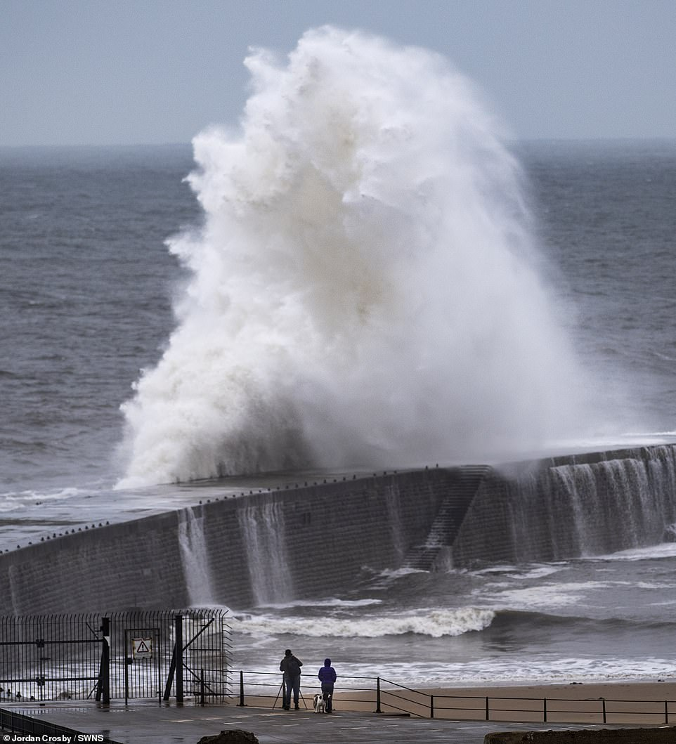 The Met Office said the UK are experiencing'unusually strong winds for September', with strong Arctic gusts coming from the north creating large waves (Pictured: couple in Seaham, County Durham)