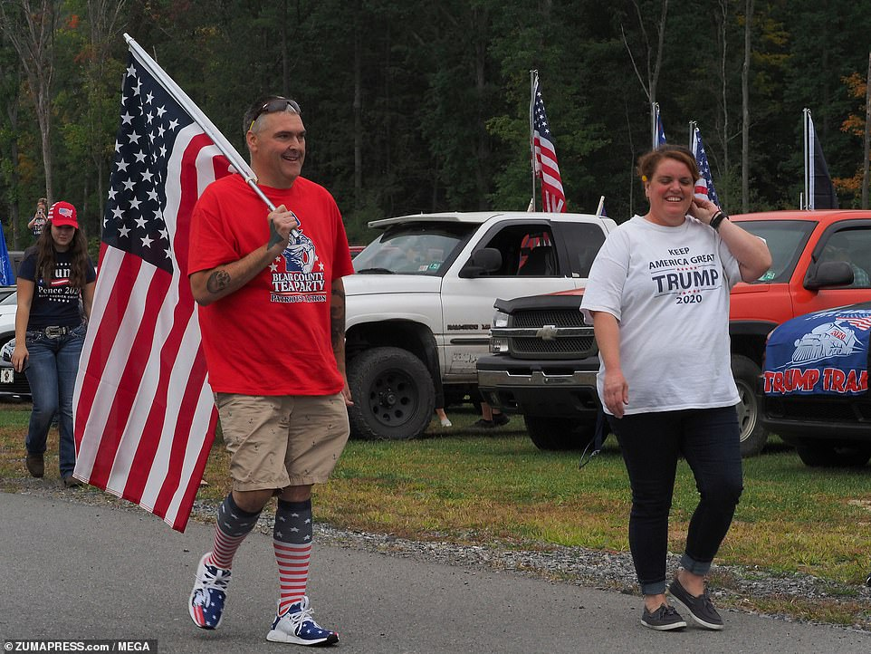 Proud Trump supporters wear t-shirts and carry American flags as part of a rally designed to show support for the president