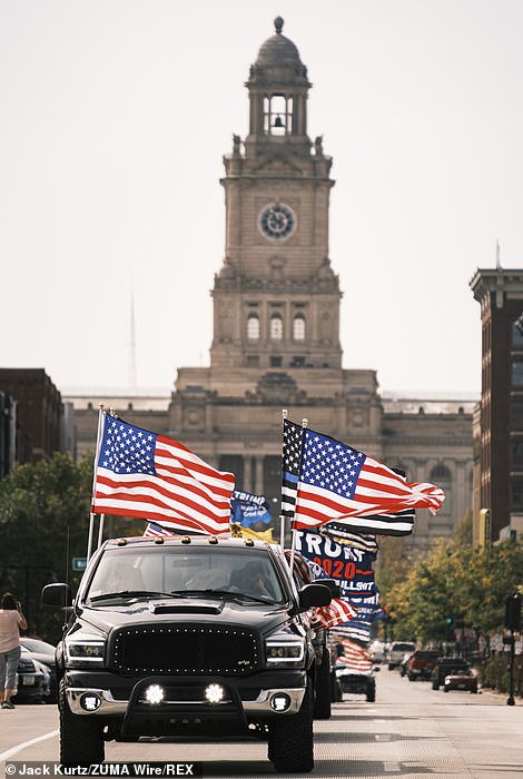 Trump supporters are seen with multiple flags hanging from their vehicles