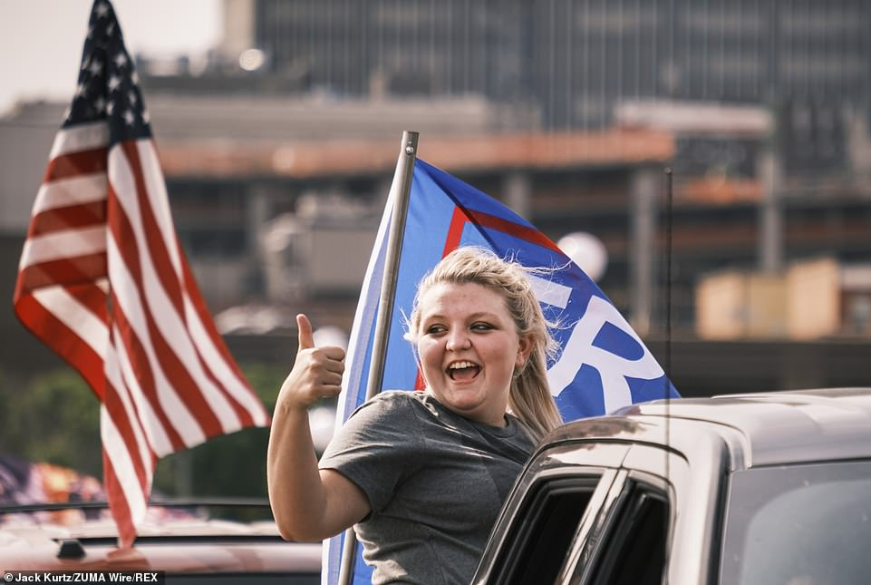 A woman in a pro Donald J. Trump motorcade gives a thumbs up as the truck she's riding in crosses the Court Avenue Bridge on Saturday