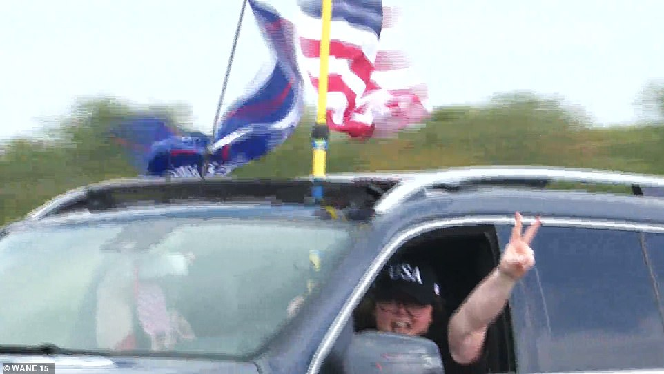 A woman wearing a USA baseball cap gives the thumbs up as she drove by as part of a massive Trump 'train' of cars and SUVs