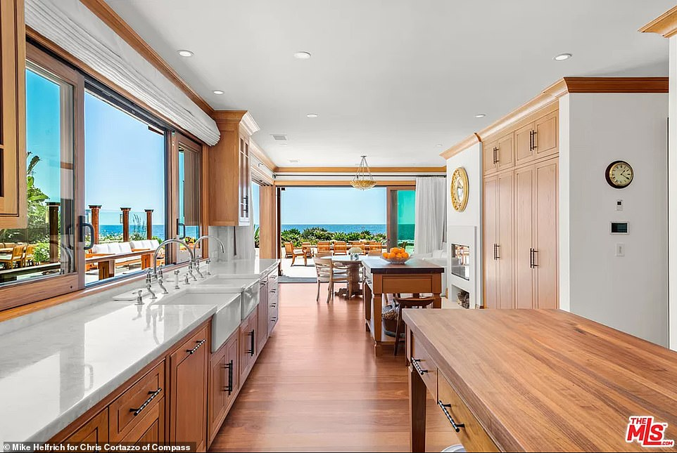 The double-island gourmet kitchen has floor-to-ceiling glass sliders that allow easy access on to the outdoor patio