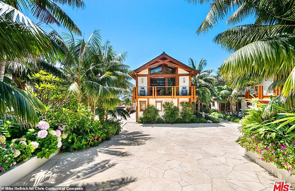 The courtyard of the home is beautifully landscaped with palm trees either side