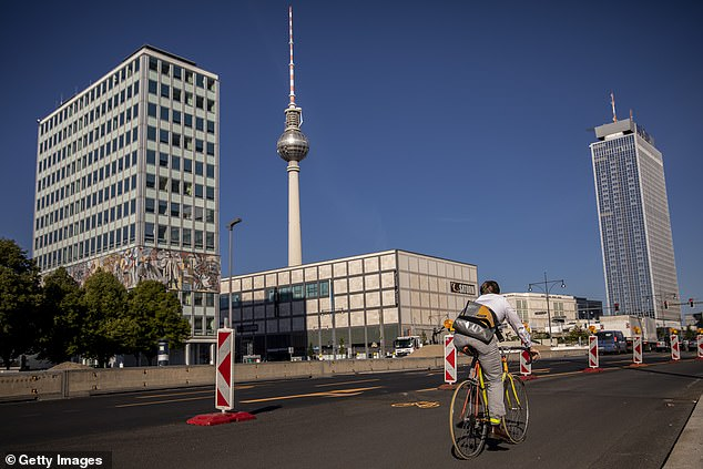 A cyclist uses a pop-up road during their morning commute near Alexander Platz in Berlin, Germany. Berlin
