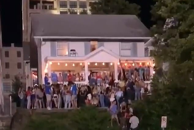 American universities are threatening strong punishments for students who violate coronavirus guidelines as alarming images of house parties and crowded college bars continue to surface. Pictured: Dozens of University of Kansas students attend a packed party near the school
