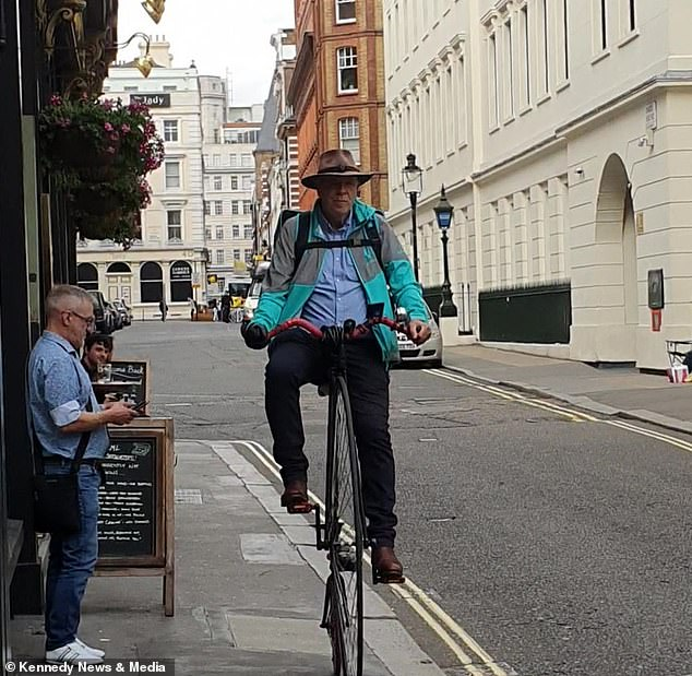 The Deliveroo worker rides the vintage penny farthing through Covent Garden in central London