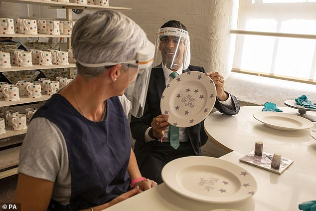 Chancellor Rishi Sunak decorated a plate during a visit to the Emma Bridgewater pottery in Stoke-on-Trent, Staffordshire on Monday, whose workers have returned from furlough.