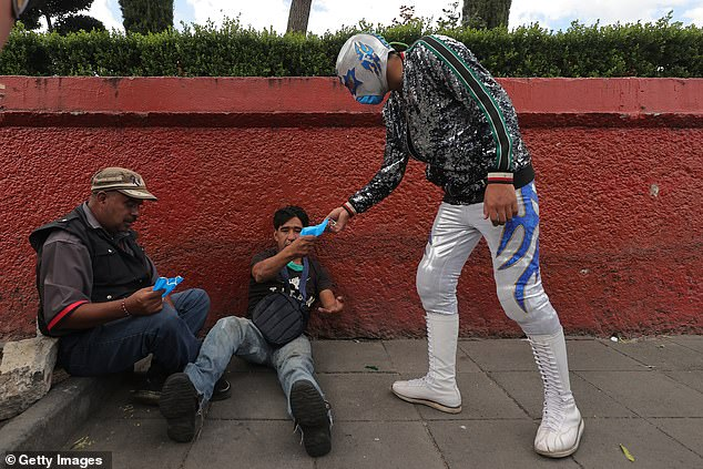 Mexican wrestler Gran Felipe Jr. hands out face masks to people on the street as part of a local campaign to promote the use of face masks to combat the COVID-19 pandemic in the Mexico City borough ofXochimilco