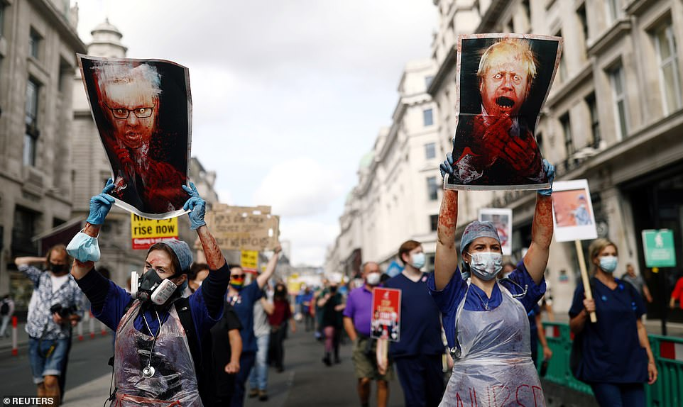 Frontline NHS workers, many of whom have been helping to fight the coronavirus pandemic, protest in London today demanding better wages. Protesters hold pictures ofPrime Minister Boris Johnson and the Chancellor of the Duchy of Lancaster Michael Gove during the demonstration