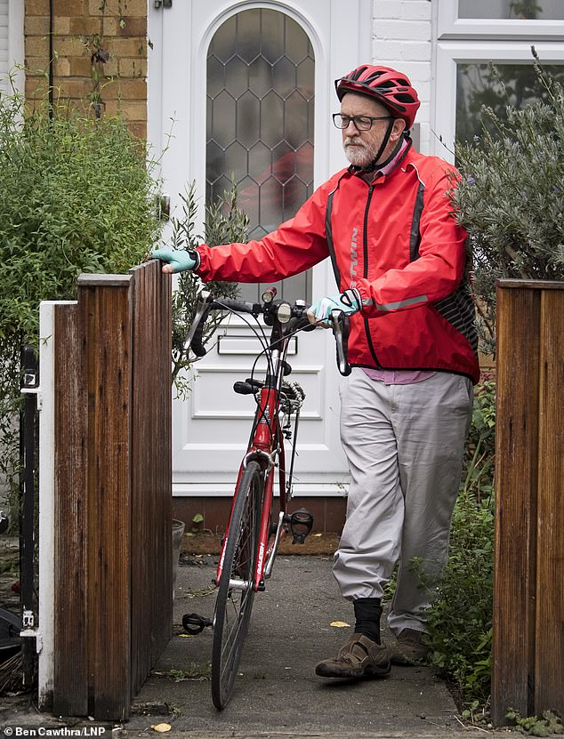 On his bike: Jeremy Corbyn takes his bicycle from his house in north London for a ride