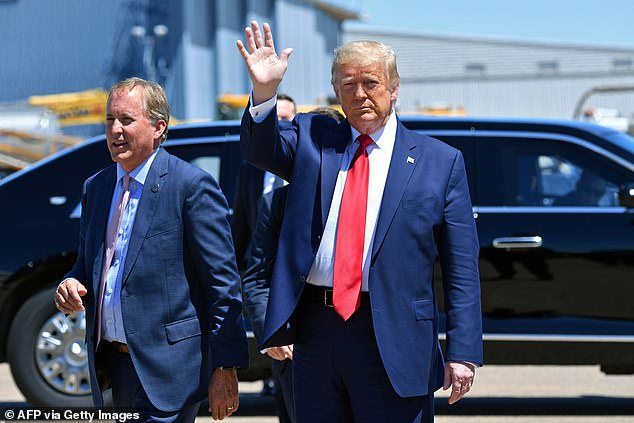 Donald Trump waves alongside Attorney General of Texas Ken Paxton in Dallas on June 11
