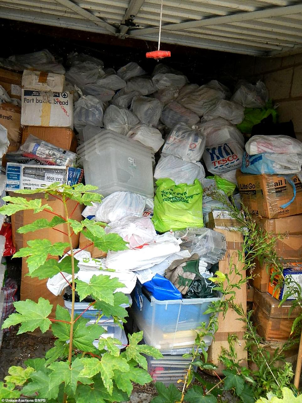 Items piled to the ceiling in the garage in of of the garages the hoarder rented. Neighbours reported the man receiving a van full of parcels every week