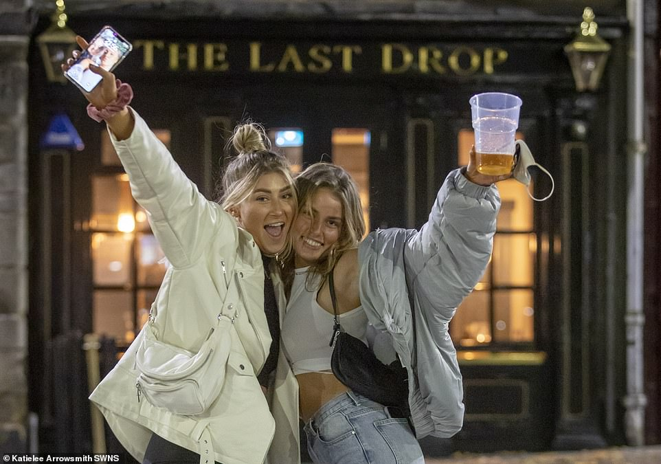 A woman holds up her phone as her friend brandishes her near-empty pint in Edinburgh on Thursday night ahead of new restrictions
