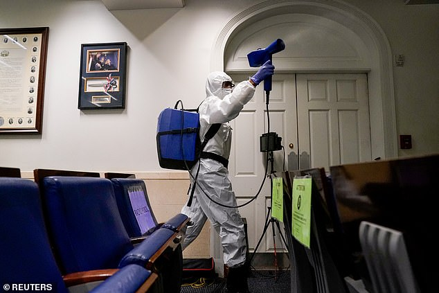 A member of the White House cleaning staff sprays the press briefing room; at least 14 people connected to President Trump have tested positive for COVID