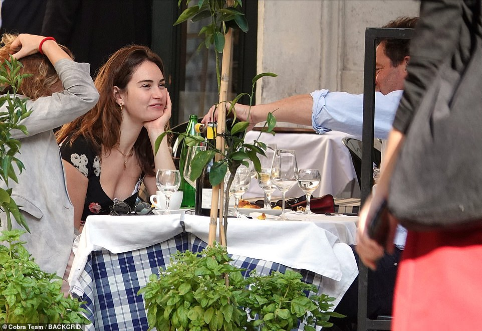 Giggling: He was showing her his phone as the pair smiled their way through dinner