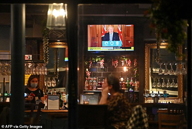 A television shows Prime Minister Boris Johnson speaking from 10 Downing Street in London, as customers sit at the bar inside the William Gladstone pub in Liverpool yesterday evening