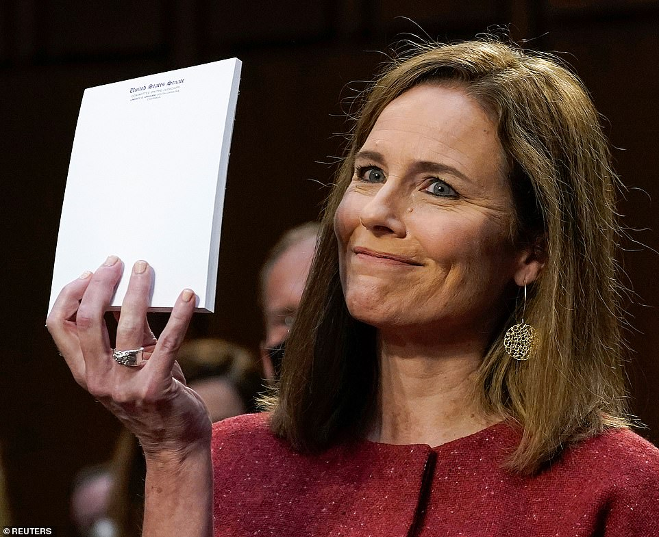Look no notes! Coney Barrett was asked to show what materials she was relying on as she was questioned and held up a blank notebook of headed Senate paper - which is left on the desk for all witnesses