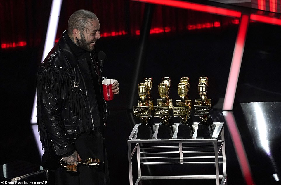 Going for the gold! Malone looked amused at the sight of the many trophies, presented to him by Kelly Clarkson on a cart