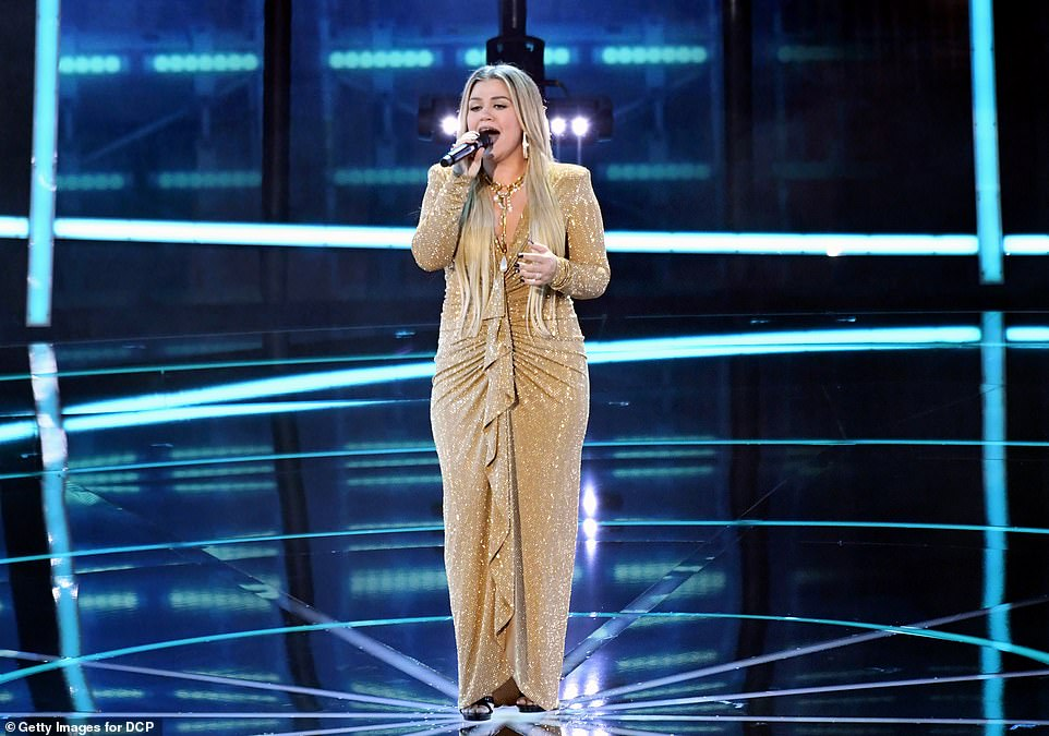 The hostess with the mostest! The show opened with host Kelly Clarkson performing Higher Love in a dazzling gold dress, before enthusiastically kicking off the ceremony to an audience-less room