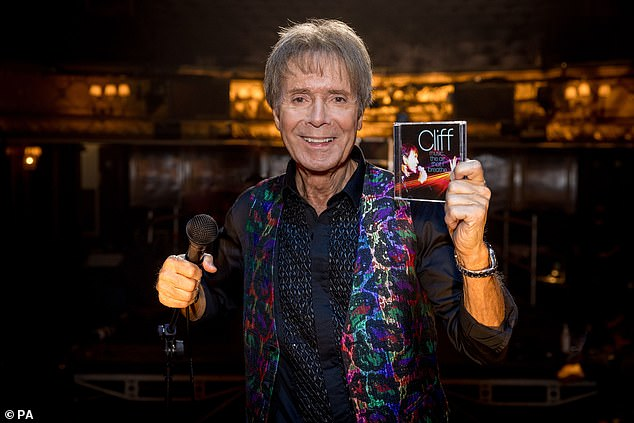 Sir Cliff proudly holds aloft his new album, released to celebrate his 80th birthday this week