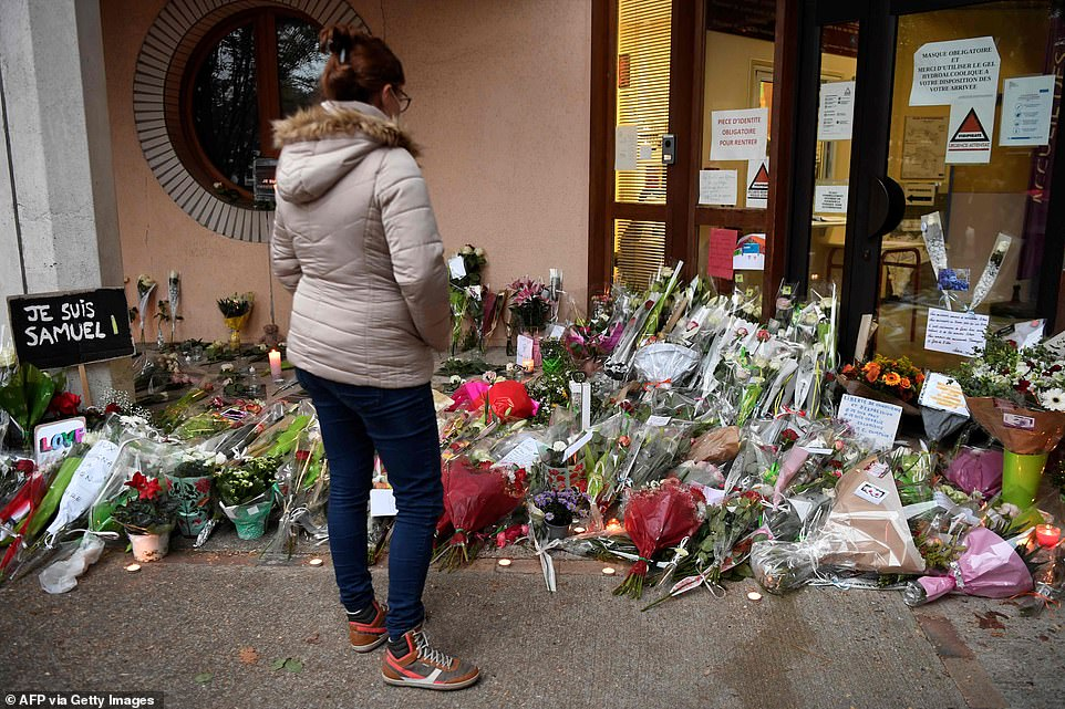 Pictured: A woman views floral tributes outside the school inConflans-Sainte-Honorine following the death of a French teacher