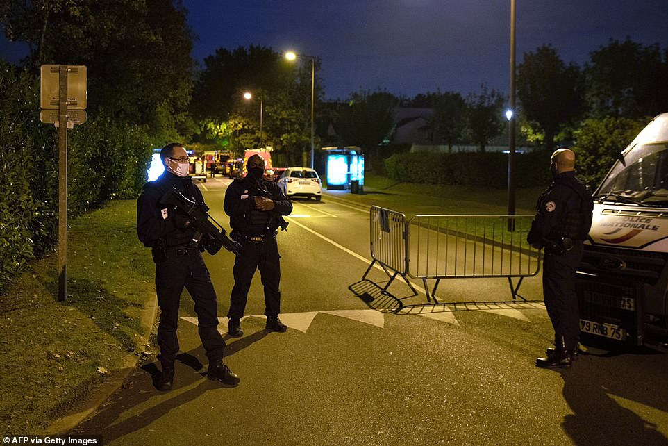 French police officers were seen standing guard and holding firearms at the end of the street where the teenager was shot dead after refusing to surrender