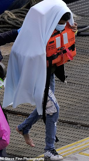 Pictured: A migrant walks off the boat without a shoe on