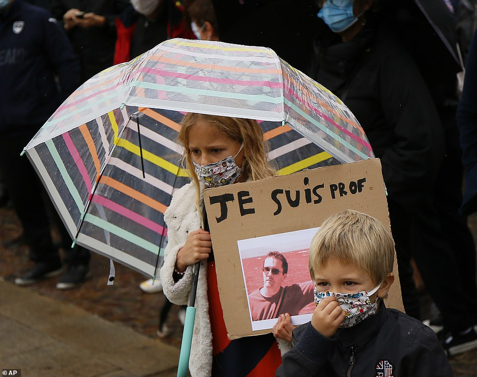A moment's silence was observed across the square, broken by applause and a rendition of La Marseillaise, the French national anthem. Pictured:A child holds up a poster of Samuel Paty that reads 'Je suis prof', 'I'm a teacher'