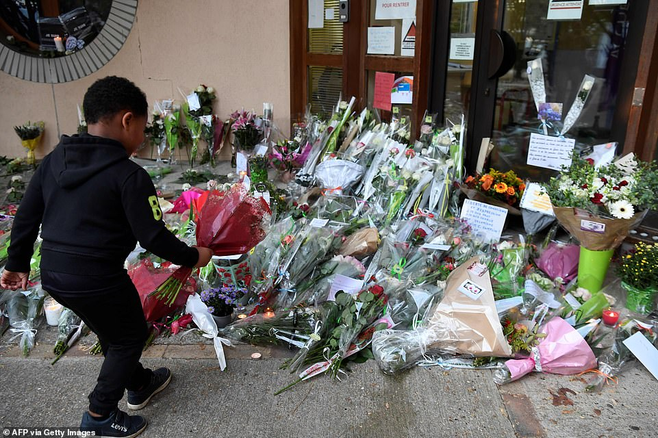 A child lays flowers on Saturday at the school in the western Parisian suburb ofConflans-Sainte-Honorine
