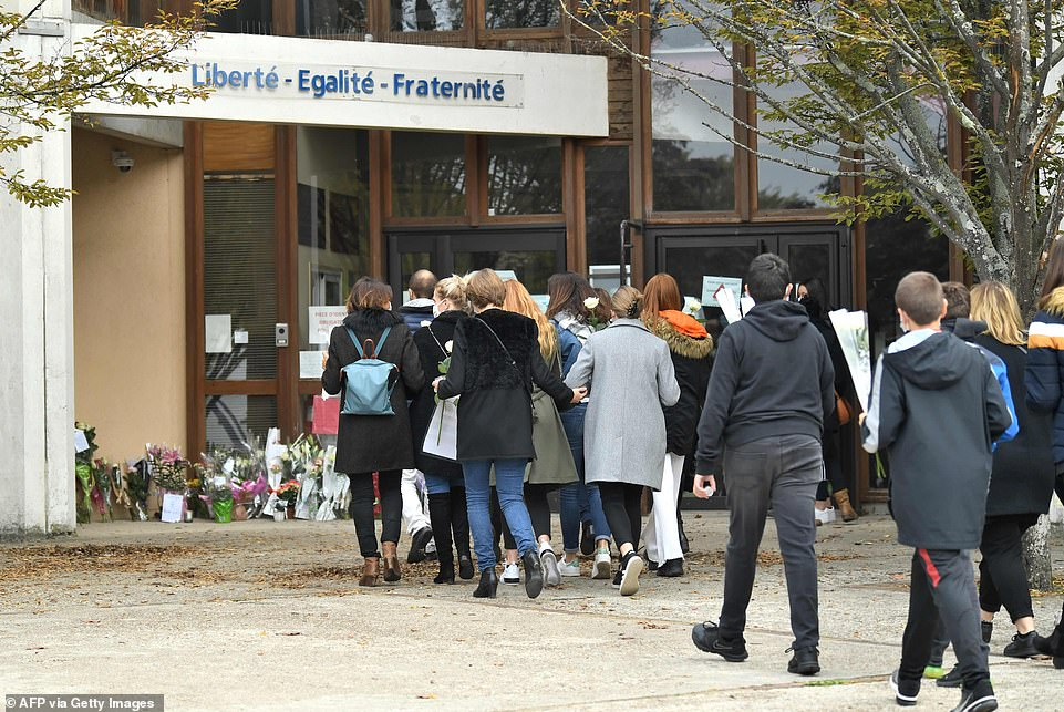 Teenagers arriving to lay flowers in front of Bois d'Aulne middle school to pay their respect after Mr Paty's murder