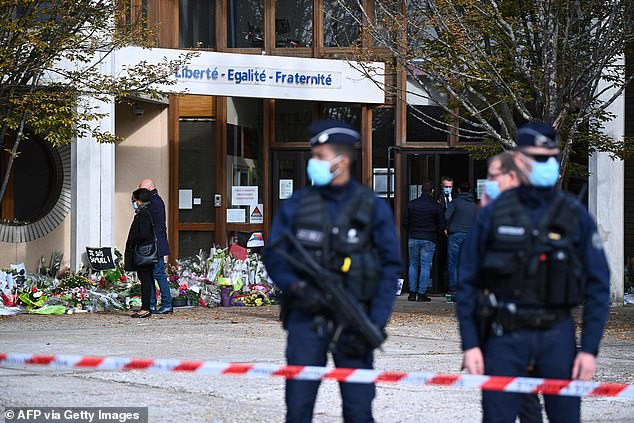 Armed police stand guard outside the secondary school where Samuel Paty taught, while mourners lay flowers at the scene alongside a placard declaring 'Je suis Samuel'