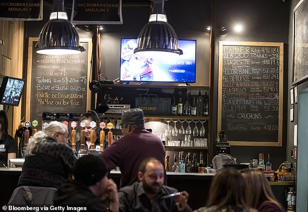 Customers sit inside Moulin 7 Microbrasserie, brew pub that honors the town's heritage, on February 9, 2018. Locals have struggled in the aftermath of the closure the mine