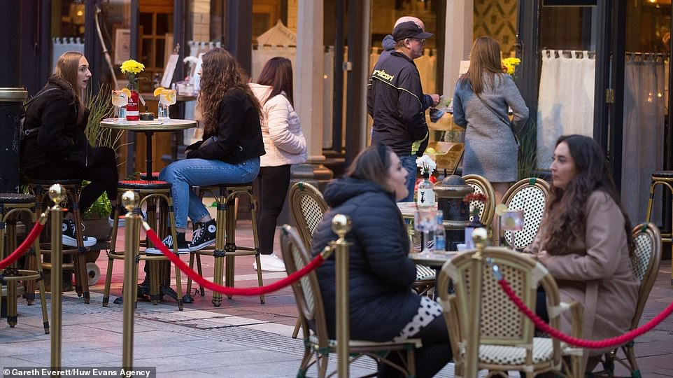 Friends sat down for a drink together in Cardiff city centre before the new firebreak lockdown comes into force today