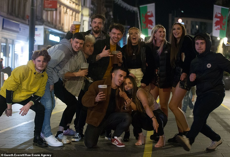 A group of young people strike a pose in Cardiff last night before the Welsh lockdown comes into place at 6pm today