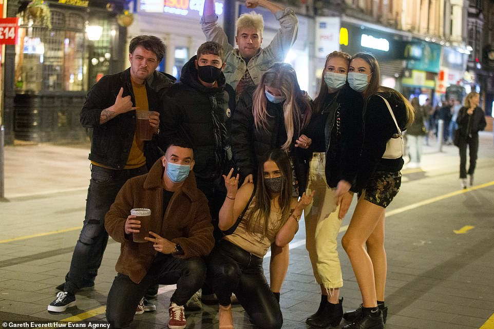 A group of revellers pose on the streets of Cardiff last night before the Welsh lockdown comes into force