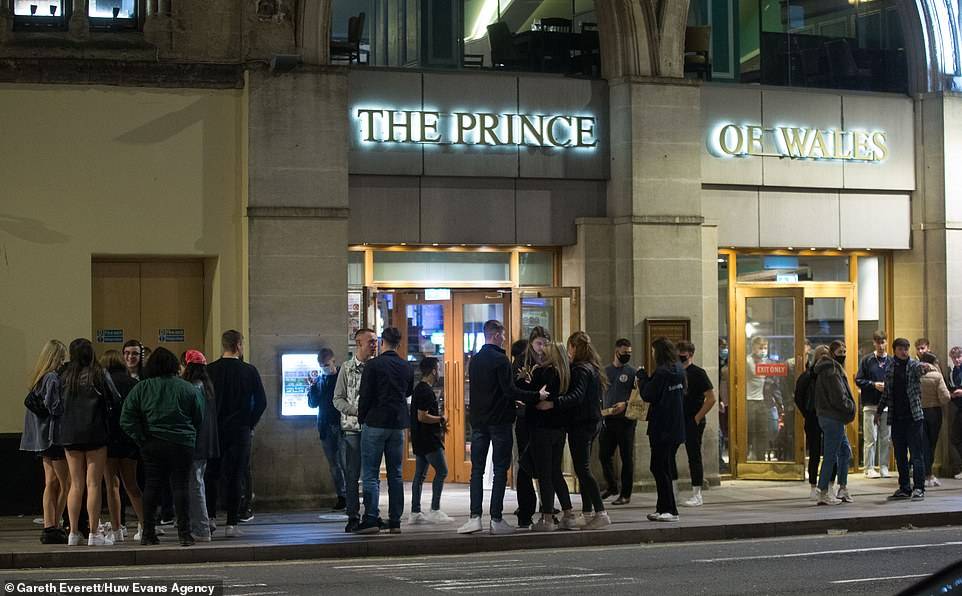 Pepole gather outside a pub in Cardiff last night before the Welsh lockdown comes into force this evening