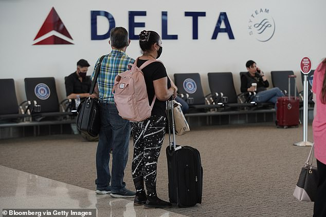 Travelers wearing protective masks wait to board a flight at the Delta Air Lines Terminal A on opening day of the Salt Lake City International Airport in Salt Lake City, Utah