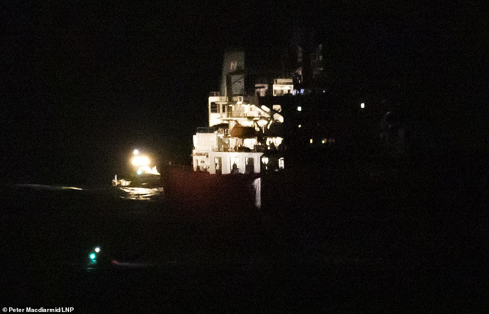 It was originally suggested that the tanker had been hijacked, but lawyers representing the owners of the vessel, which had come from Nigeria, today told the BBC the incident was '100 per cent not a hijacking' (pictured:The stern of the oil tanker Nave Andromeda lit up by police boats as the SBS stormed the tanker yesterday evening)
